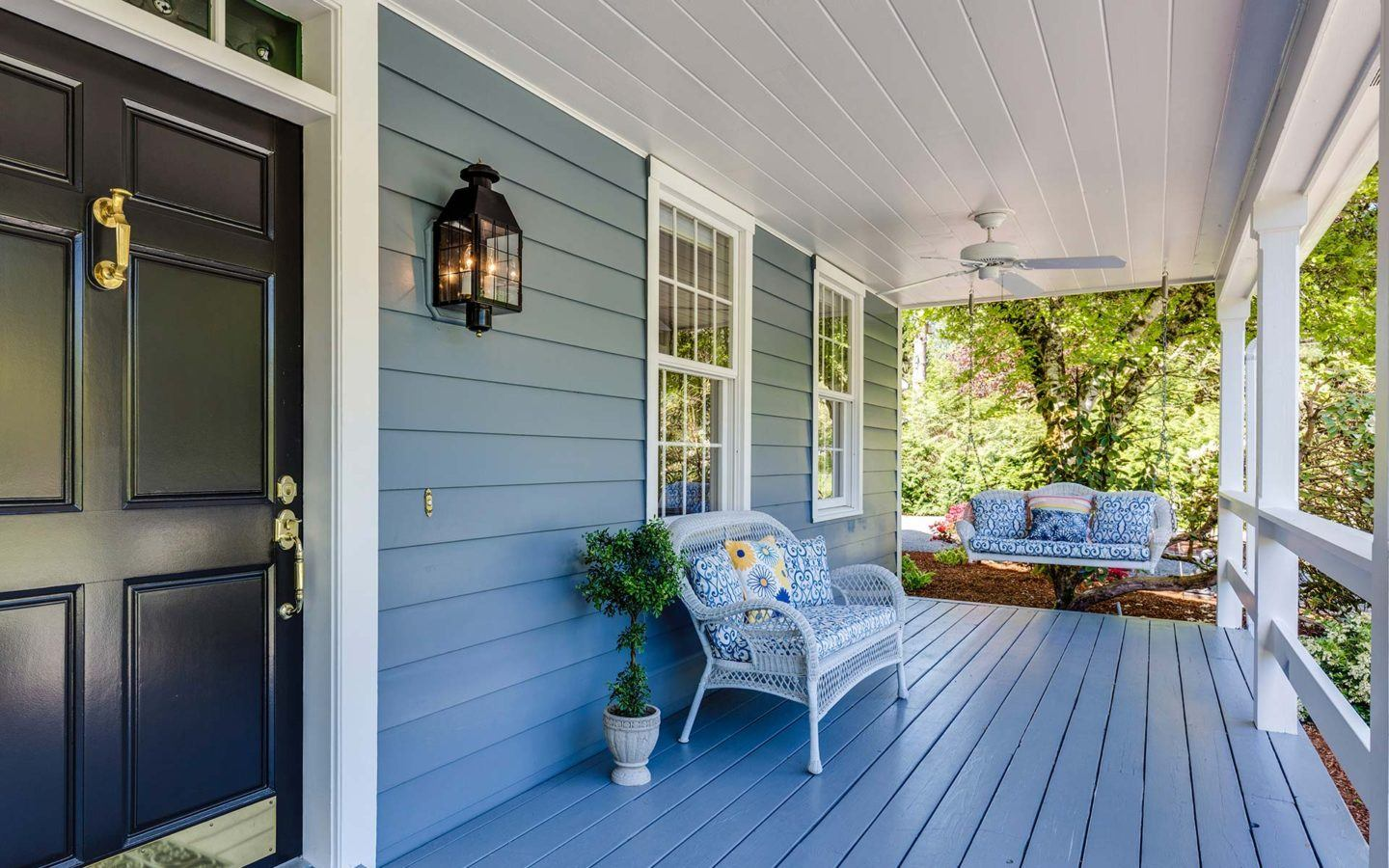 blue painted front porch and home with blue siding a porch swing and arm chair