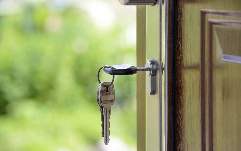 set of keys unlocking a font door of a home